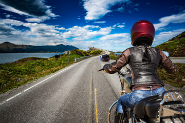 Biker girl rides a mountain road in Norway Atlantic Ocean Road. First-person view.