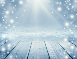 Blue wooden background and winter. Empty table and blizzard. Christmas background. Sun rays and snow. New Year background.