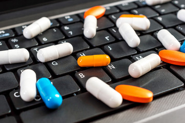 Pills on the laptop keyboard. Close up.