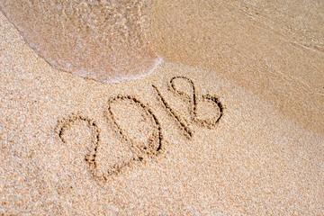 Inscription 2018 on the sand on the sea shore
