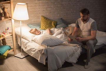 Full length portrait of father reading bedtime story to son at night sitting on edge of bed in dim lighting, copy space