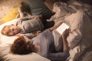 High angle portrait of mother and son falling asleep after reading book together from tablet lying in bed in dim lamplight