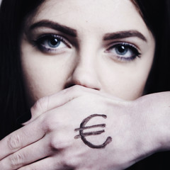 The eyes of a young beautiful woman closes her hand with the symbol of money as a symbol of a desire to be successful and to be rich. (Purposefulness, persistence, aspiration, wealth concept)