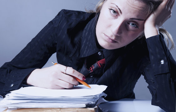 I hate my office work. Young businesswoman working with documents. Low wages, overtime working hours, lack of career prospects. (Body language, gestures, psychology)