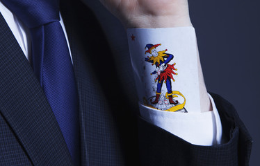 A partial view of a businessman with a Joker card in a sleeve as symbol of cheating and dishonest games (Business, fraud, profit, crime, money laundering concept)