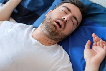 Man snoring in bed suffering for sleep apnea syndrome