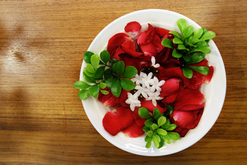 Red rose petals and green leaves with white jasmine flowers in a bowl with fresh water on wooden table
