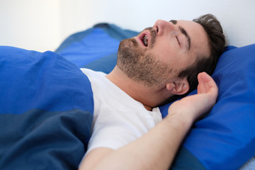 Man in bed snoring and suffering for sleep apnea syndrome