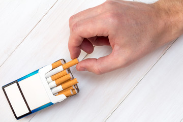Hand takes a cigarette out of pack