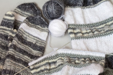 Hand knitting warm scarf and mittens made from natural mohair knitted yarn. Traditional winter needlework