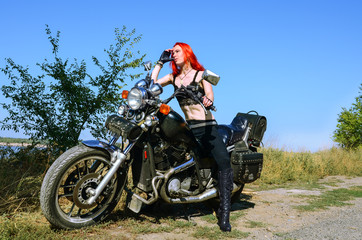 Red hair biker girl sitting on the motorcycle