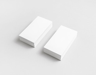 Photo of blank white paper business cards with soft shadows. Mock up for branding identity for designers.