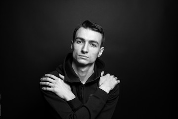 Black and white portrait of a young man in a black sweatshirt, hands crossed on the chest, against plain studio background.