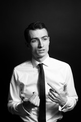 Black and white portrait of a young man in a shirt and black tie, looking to the side while explaining smth with his hands, against plain studio background
