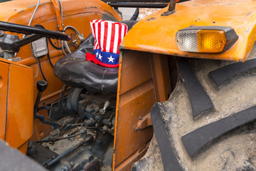 Close-up of an old rusty orange tractor with an american uncle sam hat with stars and stripes on the driver seat