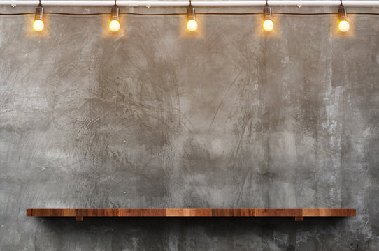 Empty brown wood plank board shelf at grunge concrete wall with light bulb string party background,Mock up for display or montage of product or design