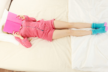Woman wearing cute pink pajamas reading in bed