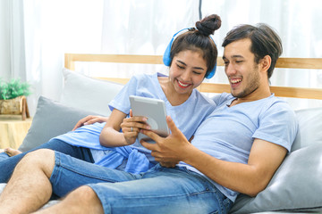 Happy asian couple lying on the bed. Lover using smart tablet listen music and shopping online together in bedroom. concept of family relax in living room.