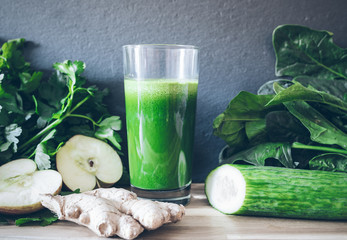 fresh green healthy detox juice in glass surrounded by vegetables and fruits