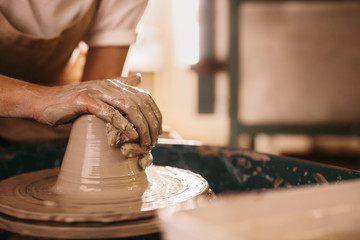 Potter moulding clay on pottery wheel