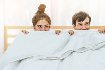 Happy young lovely couple lying in bed and cover under blanket. Concept of sex, romantic and haneymoon.