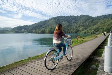 Young woman riding bicycle on Sun Moon lake bike trail