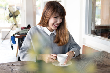 woman sit in cafe with hot cappuccino coffee on wood table during brunch. asian female have a break in coffee shop.
