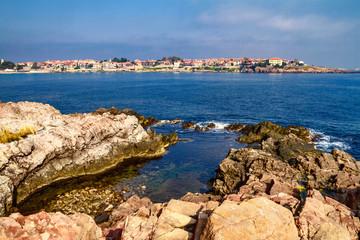 Coastal landscape - the rocky seashore with houses the sunny day, town of Sozopol on the Black Sea coast in Bulgaria
