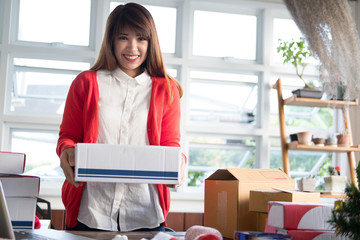startup small business owner holding parcel box at workplace. woman seller carry product for delivery to customers.  Online selling, e-commerce, shipping concept