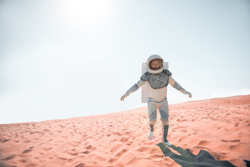 Serious spaceman wearing white armor is hardly trying to move forward on desert and looking at camera with determination. Full length portrait. Copy space on left side