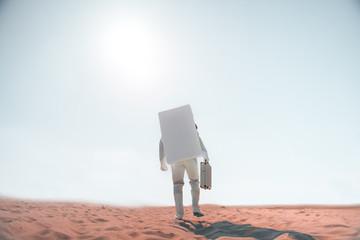 Spaceman wearing white armor is going through desert and carrying small suitcase. Focus on male back, Copy space on left side