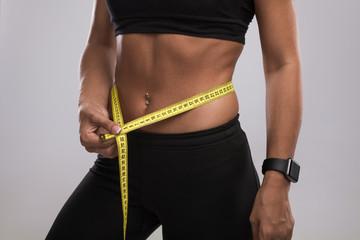 Crop woman measuring waist
