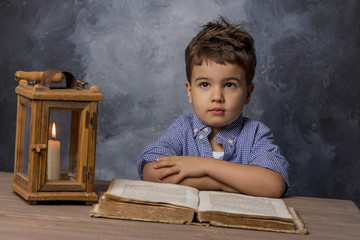 little boy with book and lantern