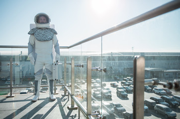 Ready for investigation. Serious astronaut wearing white helmet is standing at balcony and holding suitcase. He looking ahead with determination. Full length portrait
