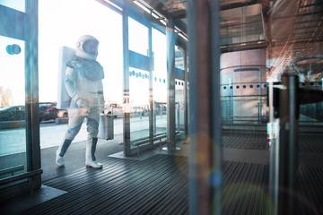 Spaceman wearing white armor is going inside terminal and carrying small case. Copy space on right side