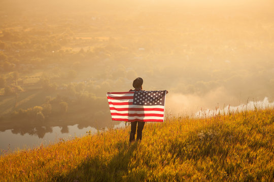 Hipster traveler with flag on nature