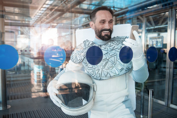 Happy spaceman is standing behind glass wall and looking at phone with bright smile. He holding special helmet. Waist up portrait. Copy space on left side
