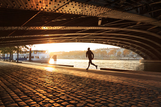 Athlete running along the river under a bridge on a sunny, autumn day. Lyon, France.