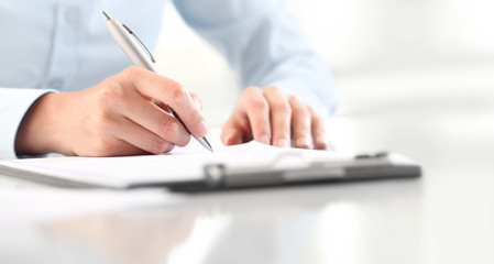 Woman's hands writing on sheet of paper in a clipboard with pen isolated on desk