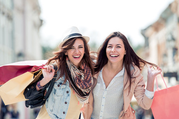 Young attractive girls with shopping bags in the city.