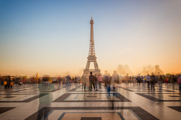 Blurred people on Trocadero square admiring the Eiffel tower at sunset, Paris, France