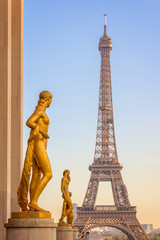 Wall Mural - Golden bronze statues on Trocadero square, Eiffel tower in the background, Paris France