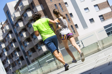 Young couple jogging for fitness in urban environment on summer day
