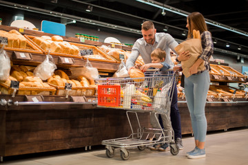 Full length portrait of happy young family shopping for groceries in supermarket together with little boy, while choosing fresh bread loaf in bakery department