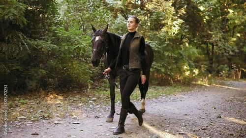 Slowmotion shot: beautiful young female jokey is walking with a stunning brown horse with white spot on forehead in the forest during sunny day in autumn