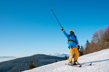Full length shot of a professional skier taking a selfie using selfie stick posing on the slope. Blue sky, mountains and winter forest on the background