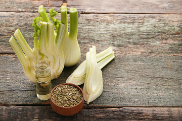 Ripe fennel bulbs with dry seeds in bowl and bottle of oil on blue wooden table