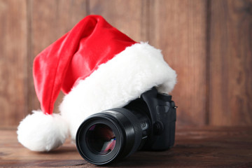 Red santa hat with camera on grey wooden table