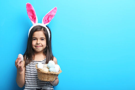 Beautiful little girl with rabbit ears and easter eggs on blue background
