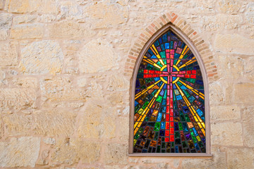 Gothic style church window with stained glass/ red cross made of stained glass